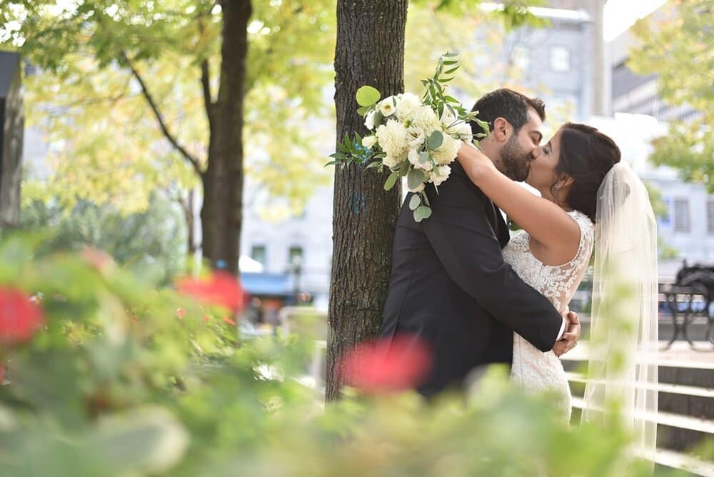 bride holding bouquet and groom kissing in the park