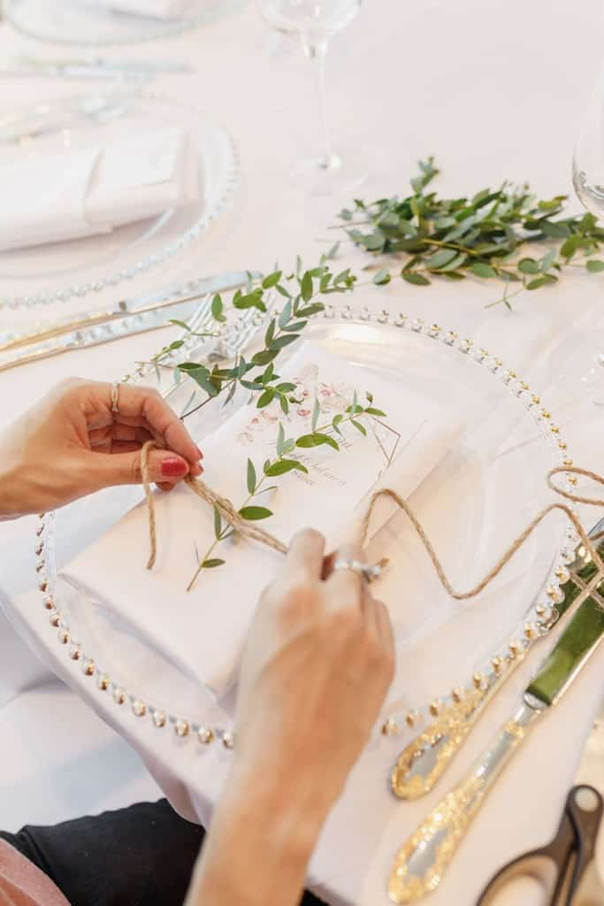 florist tying leaves to napkins for wedding