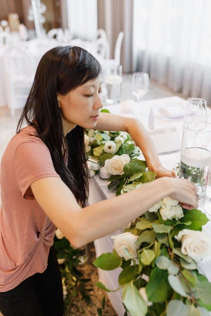 wedding florist setting up sweetheart table caryn lim